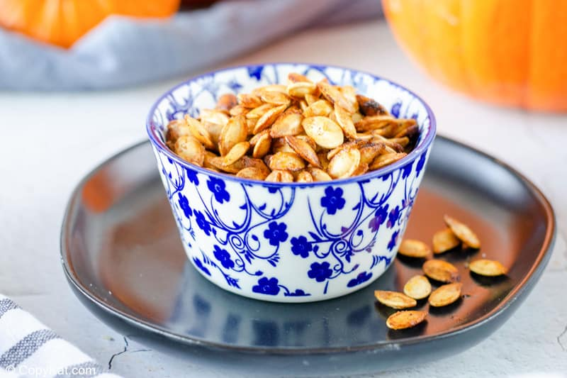 air fryer pumpkin seeds in a bowl on top of a plate.