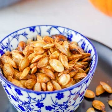 air fryer pumpkin seeds in a blue bowl on top of a black plate.
