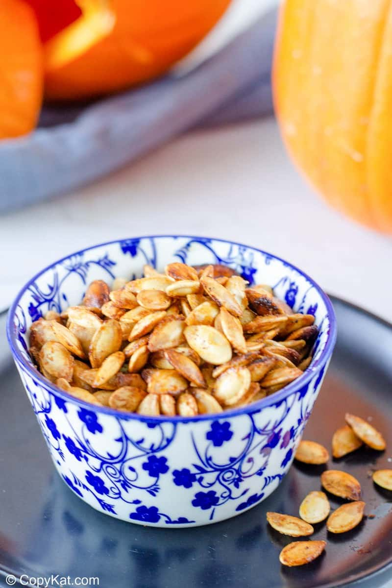 air fryer pumpkin seeds in a small blue bowl on a black plate.