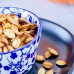 air fryer pumpkin seeds on a plate and in a bowl.