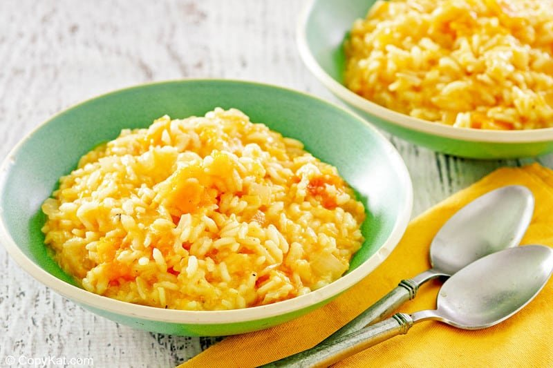 butternut squash risotto in two bowls and two spoons on a cloth napkin.