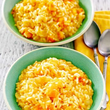two bowls of butternut squash risotto and two spoons.