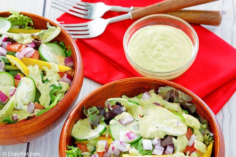 homemade Chick Fil A avocado lime ranch dressing in a bowl and on two salads.