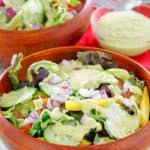 homemade Chick-Fil-A avocado lime ranch dressing on a salad and in a small bowl.