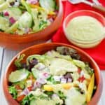 homemade Chick Fil A avocado lime ranch dressing on salad and in a bowl.