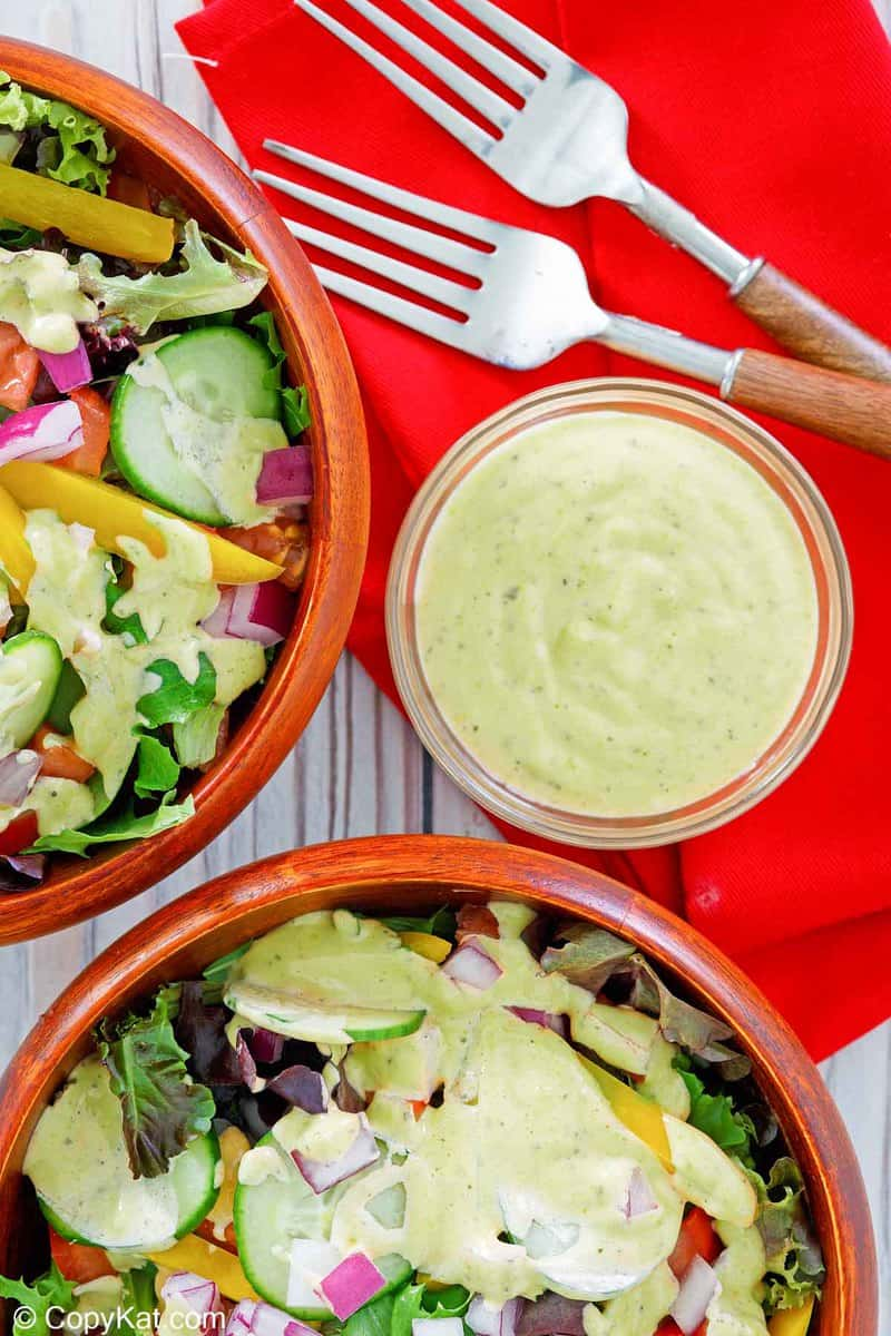 homemade Chick Fil A avocado lime ranch dressing in a bowl and on salads.