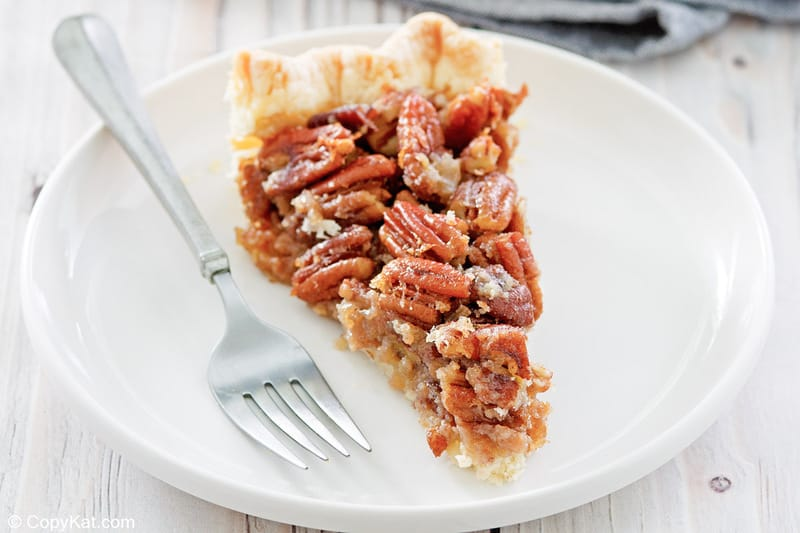 homemade Karo pecan pie slice and a fork on a plate.