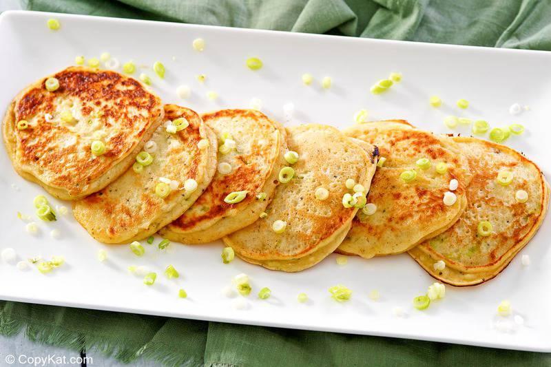 six fried mashed potato pancakes on a platter.