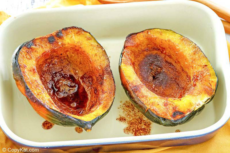 microwave acorn squash with butter brown sugar sauce in a serving dish.