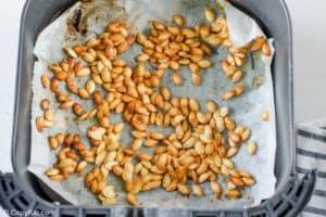 air fried pumpkin seeds in an air fryer basket.