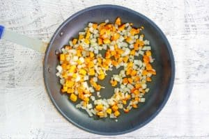 sauteed diced butternut squash and onions in a skillet.