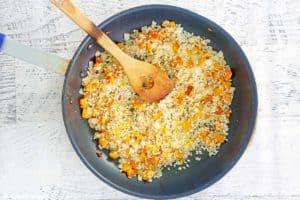 sauteed diced butternut squash, onions, and rice in a skillet.