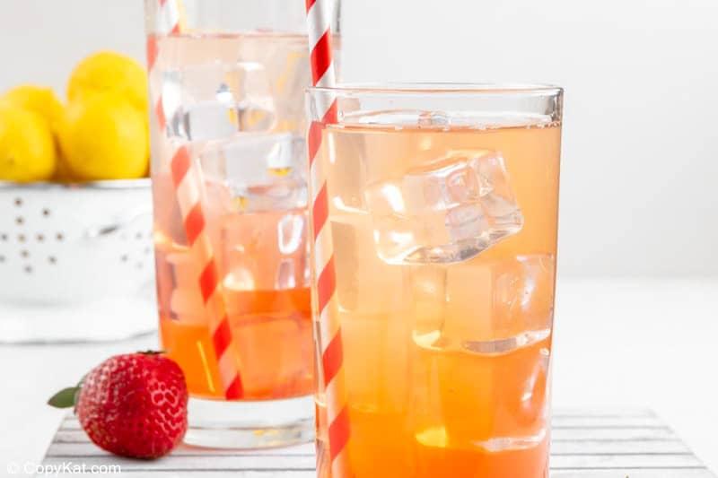 two glasses of homemade Sonic strawberry lemonade, a strawberry, and lemons.