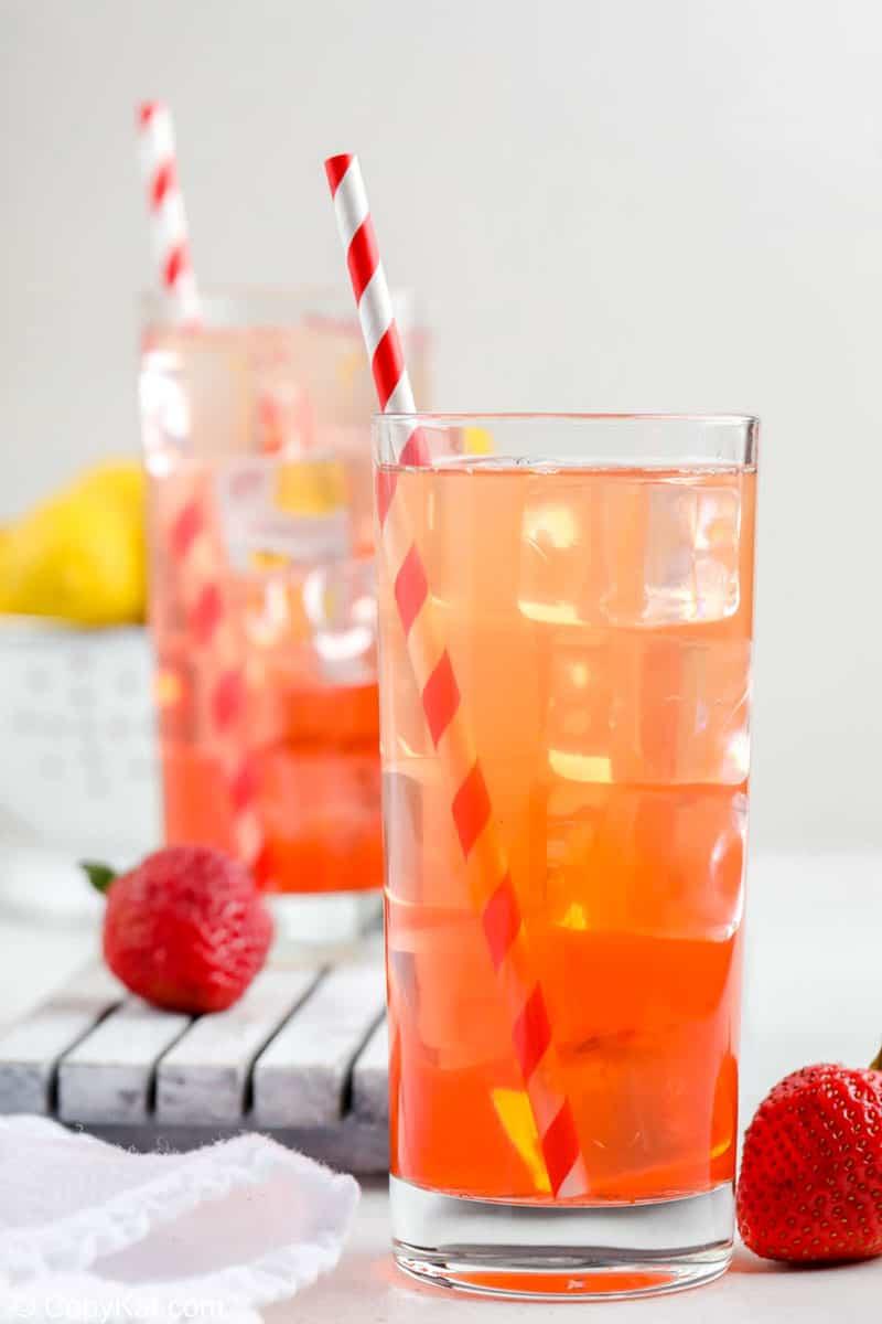 two glasses of homemade Sonic strawberry lemonade, fresh strawberries and lemons.
